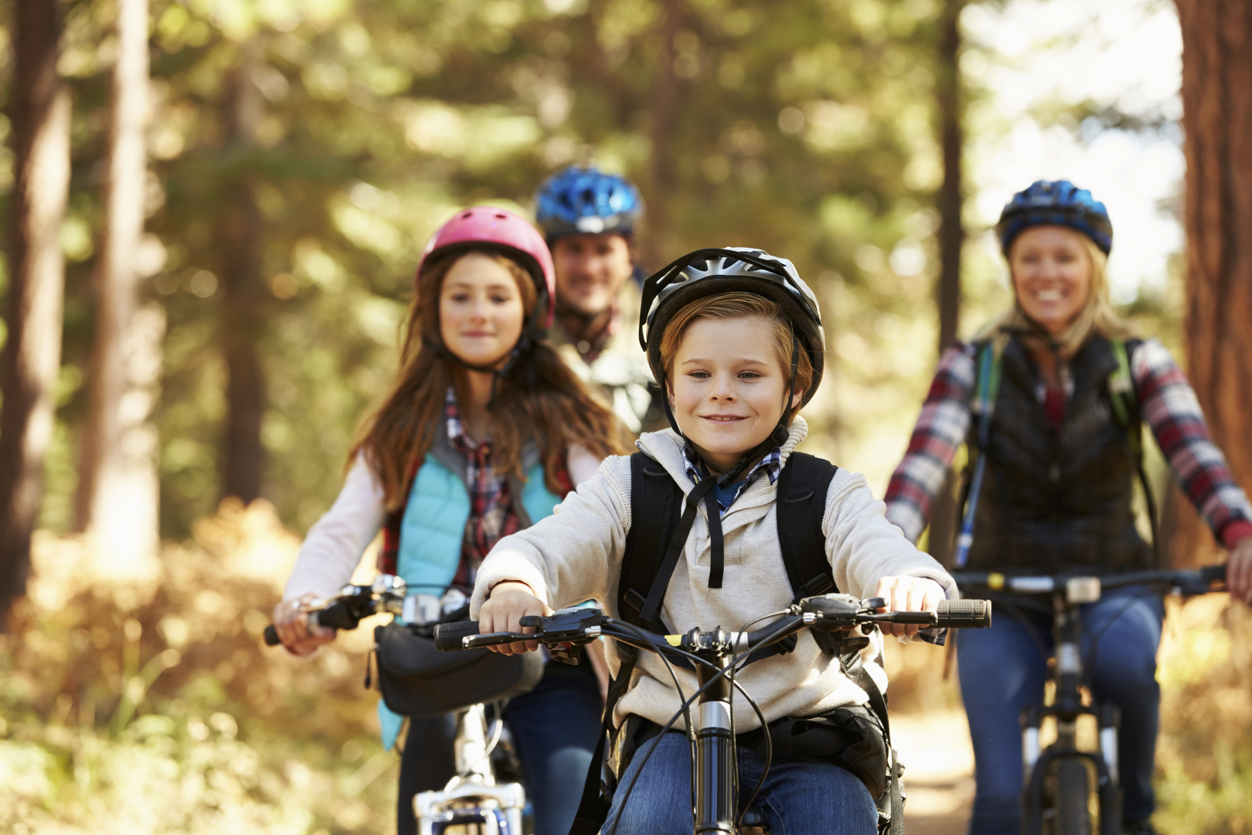 Family mountain biking on forest trail, front view, close-up
